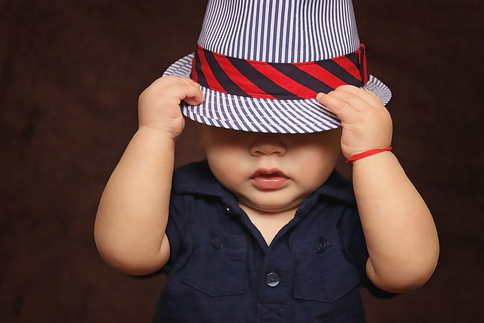 małe dziecko przymierza kapelusz